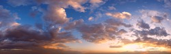 Summer sunset sky panorama with fleese clouds. Summer evening good weather sky background.