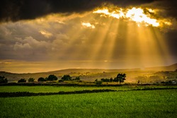 Summer sunset with sun rays through clouds, afternoon on countryside, Clouds over a farm and hills in Lancashire, England UK
