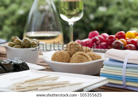 Summer tapas table with bitterballen in focus, and wine, olives and radishes in the background