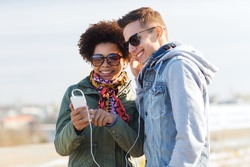 summer, technology, people and friendship concept - smiling couple with smartphone and earphones listening to music on city street