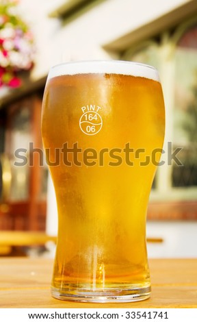 Summer thirst - pint of frosted golden beer on the terrace at the Irish pub.