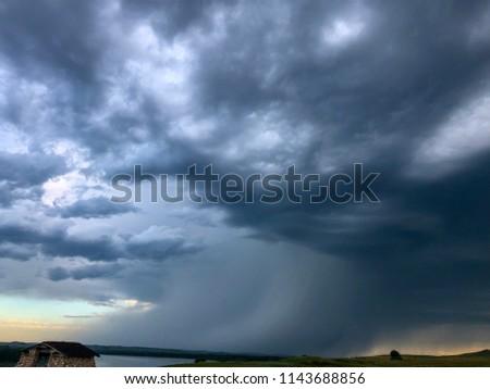 Summer thunderstorm moves across the prairie at sunset. #1143688856