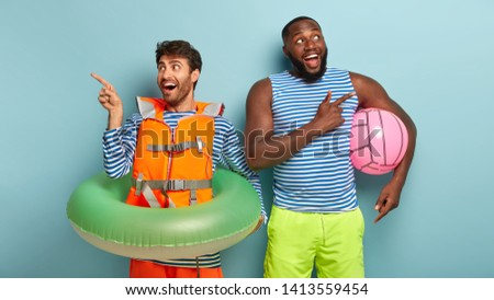 Summer time and recreation concept. Glad mixed race men point at different directions, dressed casually, spend free time on beach, use inflated ring and beach ball, invite you, enjoy water attractions
