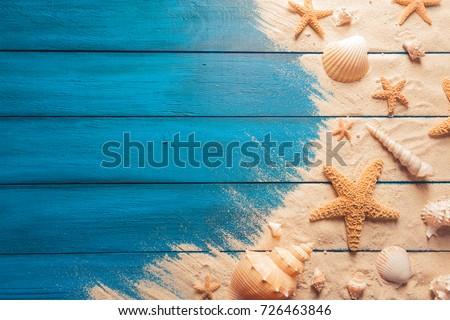 Summer time concept with sea shells and starfish on a blue wooden background and sand