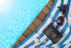 Summer time in vacation holiday,Glasses, shell, camera and towel on ocean blue wooden with blue water pool swimming in the hotel.