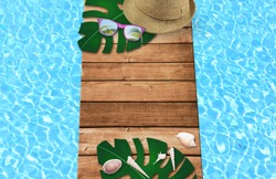 Summer time in vacation holiday, sunglasses, shell with hat on wooden floor and blue swinmming pool in the hotel. Empty space you can place your text or information.