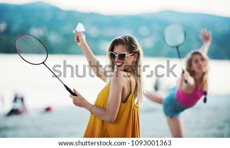 Summer time. Two young girls playing badminton and enjoying in a good mood on the summer beach. Lifestyle, vacation, sport and fun concept
