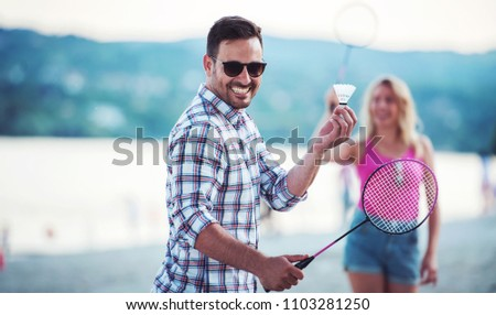 Summer time. Young couple playing badminton and enjoying in a good mood on the summer beach. Lifestyle, vacation, sport and fun concept