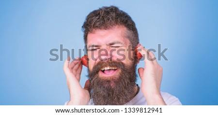 Summer top radio chart. Summer hit concept. Guy enjoy juicy sound summer hit song music. Hipster beard listen music strawberry earphones. Man bearded hipster red ripe strawberry ears as headphones.