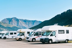 Summer tourism with RV in the mountain. Campers parked in a row in a caravan parking area. Best option for travel. Motorhomes and campingcar.