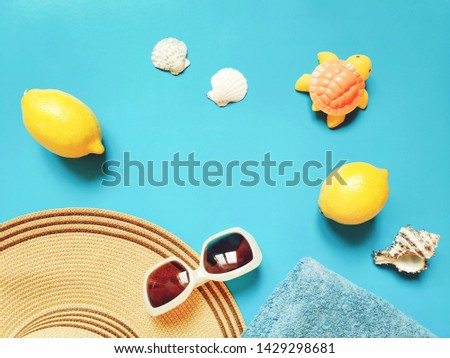 Summer travel mockup and banner. Women's sun beach hat, lemons, towel, seashells and rubber toy turtle on a blue background. Flat lay composition photography, top view picture
