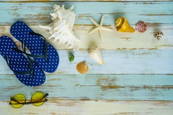 summer travel vacation background of flipflops sunglasses sea shell and star fish on blue wooden board. concept of summer travelling for vacation to island or seaside resort
