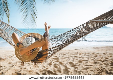 Summer travel vacation concept, Happy traveler asian woman with white bikini relax in hammock on beach in Koh mak, Thailand