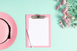 Summer trendy composition. Straw hat, pink flowers, clipboard, empty white paper on light green background. Flat lay, top view, copy space