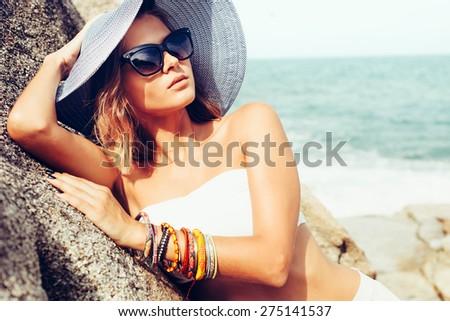 Summer trendy fashion woman posing on the rocks alone on the ocean seashore. Outdoors lifestyle portrait
