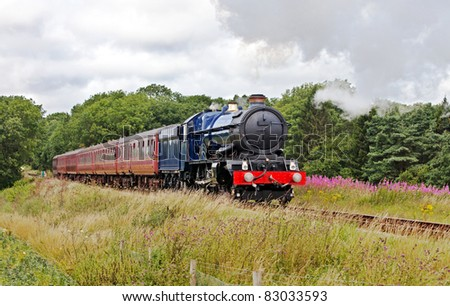 Summer trips in steam. Large blue steam train on a day trip with passengers through a summer scene