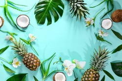 Summer tropical background with a space for a text, various fruits, green leaves and flowers arranged in a way that light shadows are fallen on the background surface, helping to keep some sum