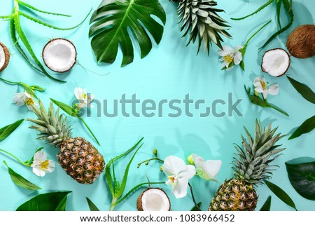 Summer tropical background with a space for a text, various fruits, green leaves and flowers arranged in a way that light shadows are fallen on the background surface, helping to keep some sum - Shutterstock ID 1083966452