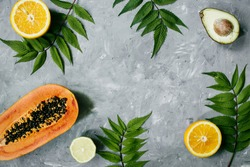 Summer tropical composition. Healthy food concept. Green leaves and tropical fruits (Papaya, orange, lemon) and avocado on gray background. Summer concept. Flat lay, top view, copy space