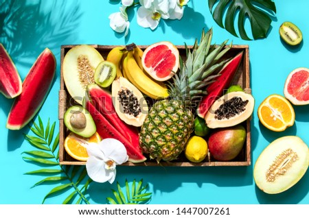 Summer tropical fresh fruits flat lay healthy table setting concept with strong contrast sunny shadow