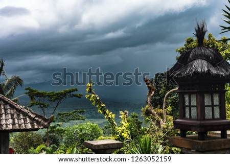 Summer tropical landscape before storm. Dark sky and gray dramatic clouds before thunderstorm on Bali, Indonesia. Wooden lamp aginst stormy cloudscape