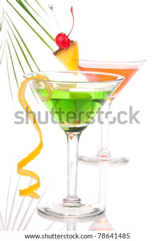 Summer Tropical Martini Cocktails with vodka, apple and peach liqueur, pineapple and cranberry juice, lime, lemon, blue curacao, maraschino cherry in cocktail glass isolated on a white background