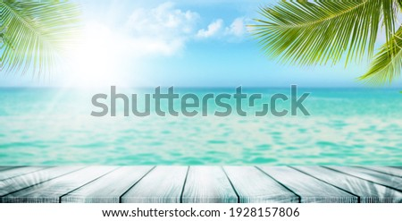 Summer tropical sea with waves, palm leaves and blue sky with clouds. Perfect vacation landscape with empty wooden table