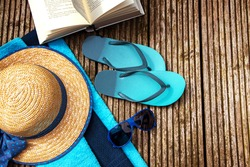 summer vacation, accessories for beach holidays as straw hat flip flops, blue sunglasses, turquoise towels and a book on a rustic wooden footbridge, view from above