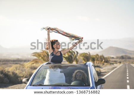 Summer vacation and travel concept image of a young woman waving headscarf out of hood of convertible car Curly brunette girl arms up having fun in a cabriolet topless. Female friends enjoying freedom