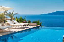 Summer vacation at poolside. Veranda decorated with deck chairs and umbrella with an ocean view