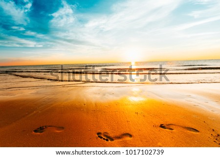 Stock Photo Summer vacation at sea. Sunset on the ocean, footprints barefoot, sky, clouds