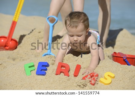 Summer vacation: Baby playing with beach toys in the sand