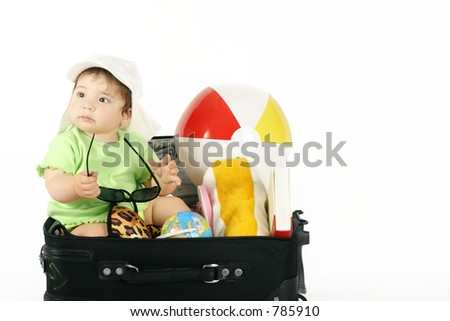 Summer Vacation - Baby sitting in a bag packed with beachy things.