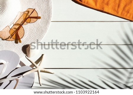 Summer vacation background of beach accessories:  sun hat, flip flops, towel,  shells and shadow of tropical palm leaves. Vacation, holiday, travel, tourism, summertime concept. Top view. #1103922164