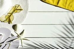 Summer vacation background of sunglasses, sun hat, shells, towel and  flip flops. Summertime, holiday, travel, beach, tourism concept. White and yellow colors.  Top view, space for text.