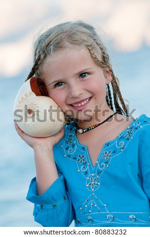 Summer vacation - beautiful girl with shell at the beach