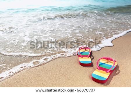 Summer vacation concept--Flipflops on a sandy ocean beach - stock photo