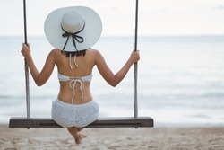 Summer vacation concept, Happy asian woman with white bikini and hat relax on swing in tropical beach, Chanthaburi, Thailand