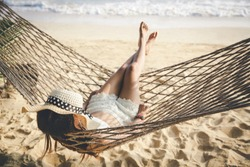 Summer vacation concept, Happy woman with white bikini and hat relaxing in hammock on tropical beach at sunset, Koh mak, Thailand