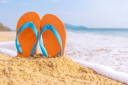 Summer vacation concept--Orange Flipflops on a sandy ocean beach