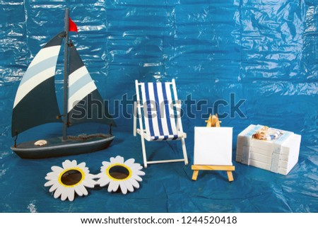 Summer Vacation Concept with toy boat with deck chair an Treasure chest on blue background