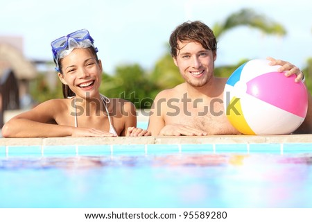 Summer vacation couple having fun in pool on sunny day in tropical resort