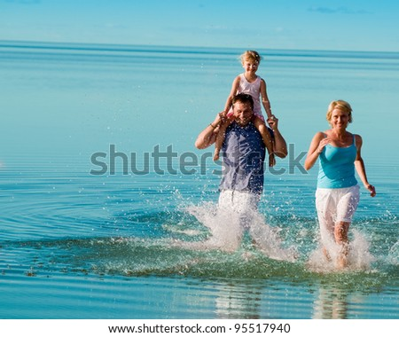 Summer vacation - family playing on the beach (space for text)