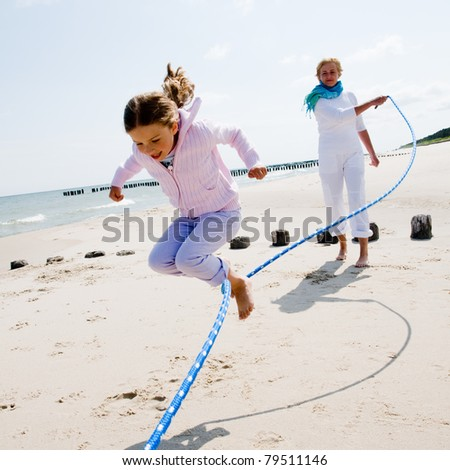 Summer vacation - family  playing with skipping rope on the beach