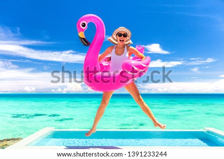 Summer vacation fun funny woman jumping with flamingo swimming pool float around waist excited of tropical hotel holiday. Foto stock ©