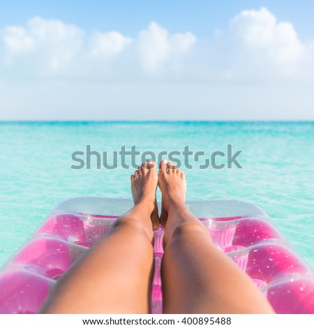Summer vacation girl lower body closeup. Woman tanning legs  relaxing in ocean on pink inflatable swimming pool air mattress bed floating in turquoise water background. Suntan at tropical beach.