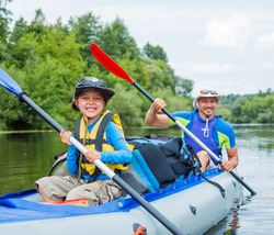 Summer vacation - Happy little boy with his father kayaking on river.