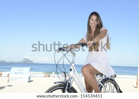 Summer vacation: Happy woman with bike on the beach