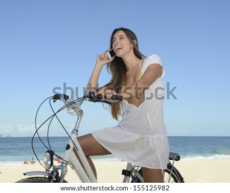 Summer vacation: Happy woman with bike on the beach talking on phone