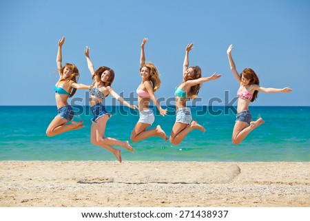 summer, vacation, holiday, happy people concept - a group of friends jumping and running on the beach
